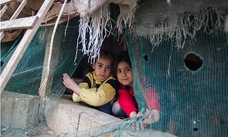 Esma, 7, and a friend peer out of a tent in Lebanon that has been home to her family since last year